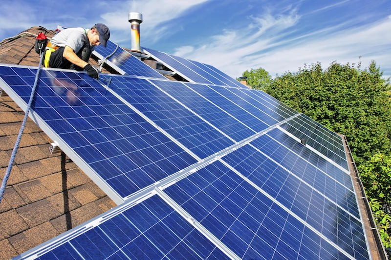 Man installing solar panel on top of roof for SolRelible